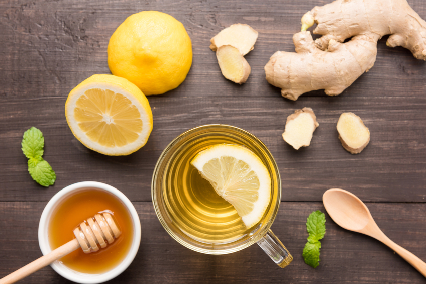 Cup of ginger tea with lemon and honey on wooden background.